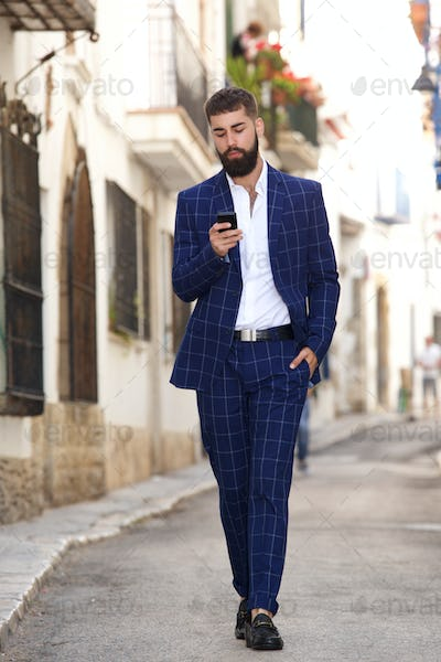 Full length businessman walking in city street with cell phone