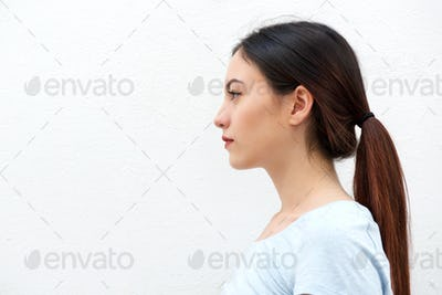 Side portrait of casual young woman standing alone