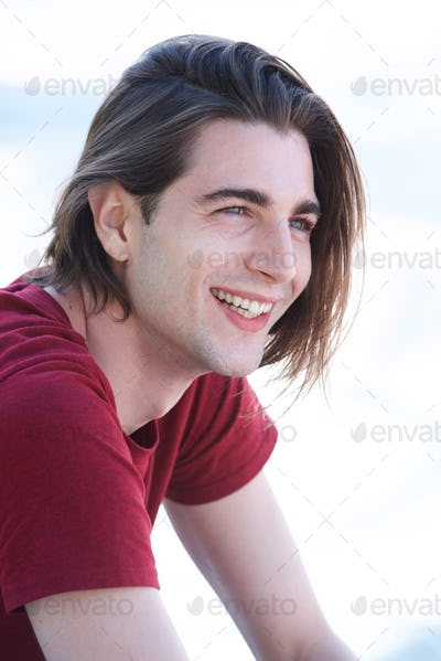 Close up handsome young man with long hair laughing