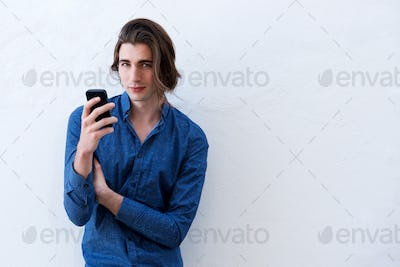 Handsome young man standing and holding smart phone
