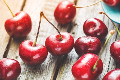 Macro photography of ripe cherry berries over wooden table. The concept of healthy organic food.