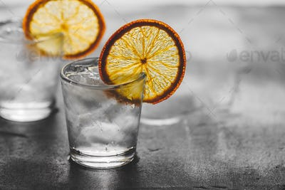 Two shots of tequila with ice and a dried orange slice on a grey background.