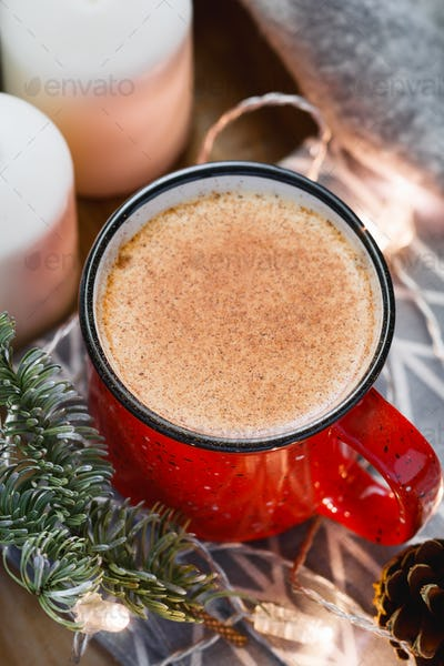 Close up of an eggnog traditional Christmas drink surrounded festive and winter details.