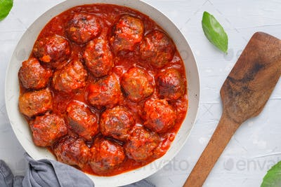 Meatballs with tomato sauce in a white iron pan over white background. Modern style. Top view.