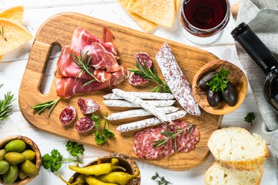 Italian antipasto with salami, jamon and olives on white