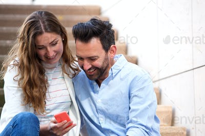 Close up cheerful couple sitting on steps together with mobile phone