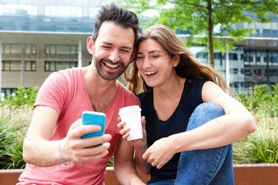 Close up happy young couple sitting together with mobile phone and coffee