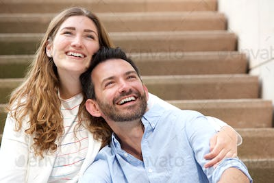 Close up happy couple sitting together on staircase in embrace