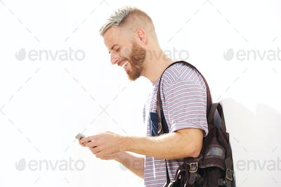 cool young guy with beard looking at mobile phone