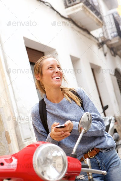 happy young woman sitting on scooter with mobile phone