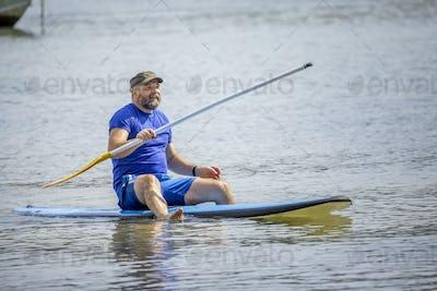 a bearded man paddling in the ocean