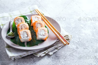 Philadelphia roll classic on a plate with chopsticks. Japanese sushi food. Copy space