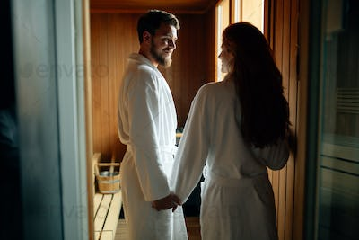 Beautiful couple relaxing in sauna