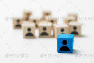 Leadership concept using blue people icon cube among other cubes