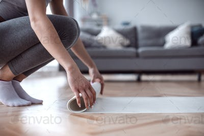 Close up woman hands unrolling mat is preparing for fitness workout at home.