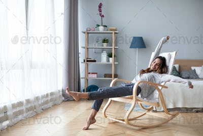 attractive pretty lady with her beaming smile she stretch oneself indoor cosy modern room.