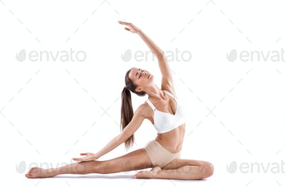 Beautiful young woman doing yoga or pilates exercise isolated on white background.