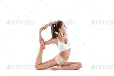 Sporty young woman doing yoga practice isolated on white background.