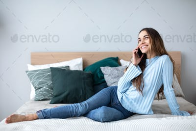 Happy woman talking on smartphone at home on the couch.