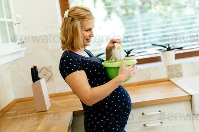 Beautiful pregnant woman preparing muffins in kitchen