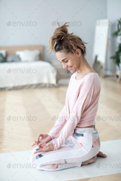 Beautiful smiling woman relaxing on yoga mat.