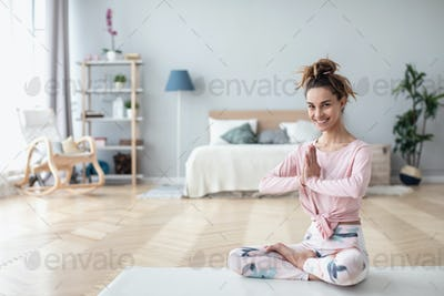 Time for yoga. Beautiful smiling woman in lotus pose on yoga mat while resting at home.