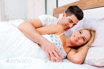 Couple having fun in bed and smiling