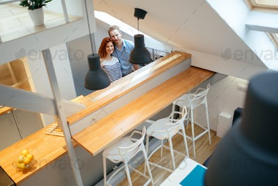Beautiful couple in well designed kitchen