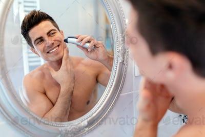Happy handsome man shaving