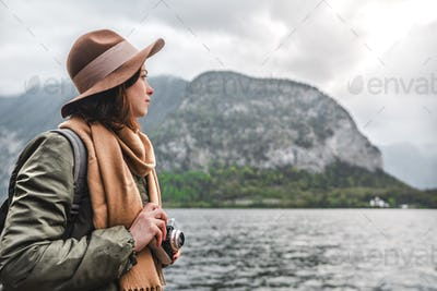 Attractive girl with a retro camera by the Austrian lake