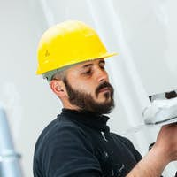 worker plastering gypsum board wall.