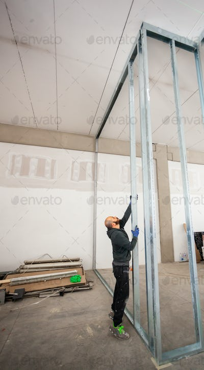 Worker builds a plasterboard wall.
