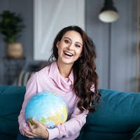 Smiling woman with model of the globe at home.