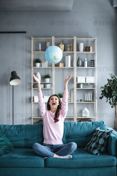 Jubilant successful young planning a vacation with world globe.