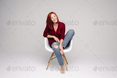 Model with ginger hair sitting on white chair in studio