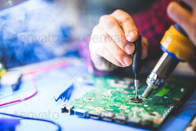 Worker fixing a main board of a computer.
