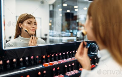 Female customer looks at the mirror in makeup shop
