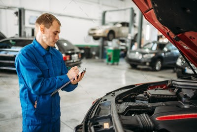 Technician fills check list, car with opened hood