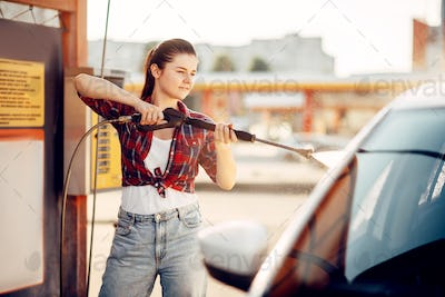 Young woman on self-service car wash