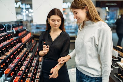 Consultant helps woman with choice in make-up shop