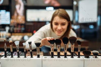 Female customer choosing brushes in makeup shop