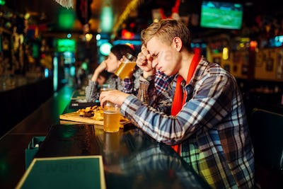 Sad fan covers face with hands in sports bar