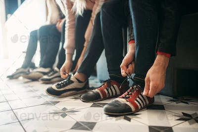 Bowling players ties shoelaces on house shoes