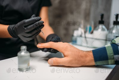 Beautician polishing nails to male client in salon