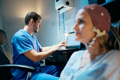 Doctor Doing Brain Medical Exam On Old Woman In Hospital