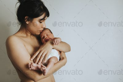 Naked mother holding her infant baby