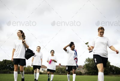 Junior female football players walking on a field
