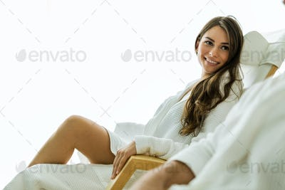 Sexy and beautiful woman relaxing in a chair dressed in a robe