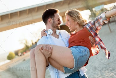 Beautiful couple hugging and dating on beach