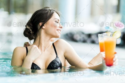 Beautiful young women drinking a cocktails in the swimming pool